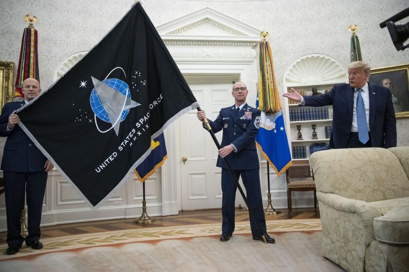 """El general John """"Jay"""" Raymond, titular del Comando Espacial de Estados Unidos, a la izquierda, y el sargento maestre superior Roger Towberman, a la derecha, sostienen la bandera de la Fuerza Espacial para mostrársela al presidente Donald Trump el viernes 15 de mayo de 2020, en la Oficina Oval de la Casa Blanca, en Washington. (AP Foto/Alex Brandon)"""