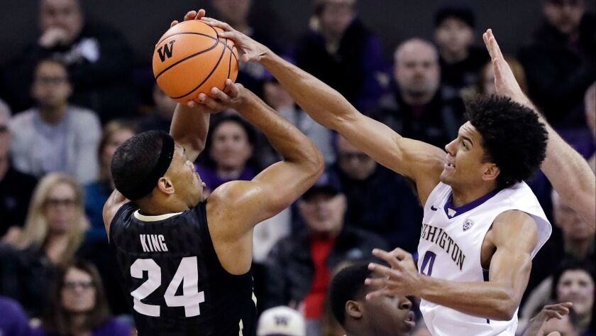 Washington's Matisse Thybulle, right, blocks a shot by Colorado's George King in the first half.