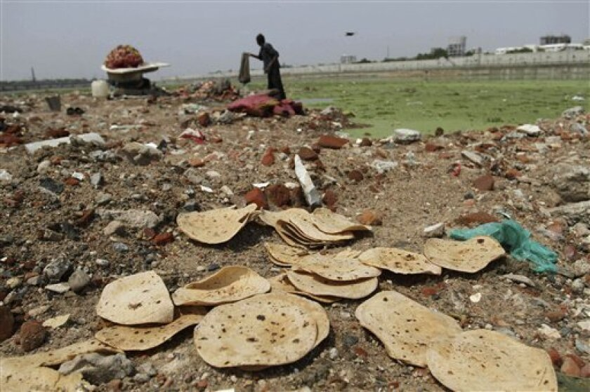 FILE - This June 5, 2013 file photo shows discarded rotis, or Indian bread, along the river bank as an Indian man cleans clothes in the polluted Sabarmati River in Ahmadabad, India. In a United Nations Food and Agricultural Organization report released Wednesday, Sept. 11, 2013 by the Rome-based food agency, one-third of all food produced in the world gets wasted, amounting to an annual loss of $750 billion ($995 billion). The report said food waste hurts the environment by causing unnecessary c