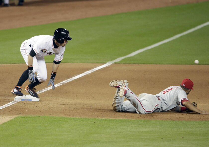 Miami Marlins' Ichiro Suzuki, left, is safe at third and goes on to score as Philadelphia Phillies third baseman Andres Blanco (4) can't get to the ball on a throwing error by catcher Carlos Ruiz the tenth inning of a baseball game, Wednesday, Sept. 23, 2015, in Miami. The Marlins defeated the Phillies 4-3 in eleven innings. (AP Photo/Lynne Sladky)