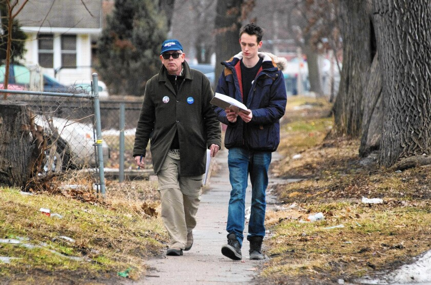 Volunteers Bob Swope, left, and Fergus Wilson canvass for Bernie Sanders in Des Moines on Jan. 31. Swope, a former Occupy protester, drove four hours to the city last week to work for Sanders.
