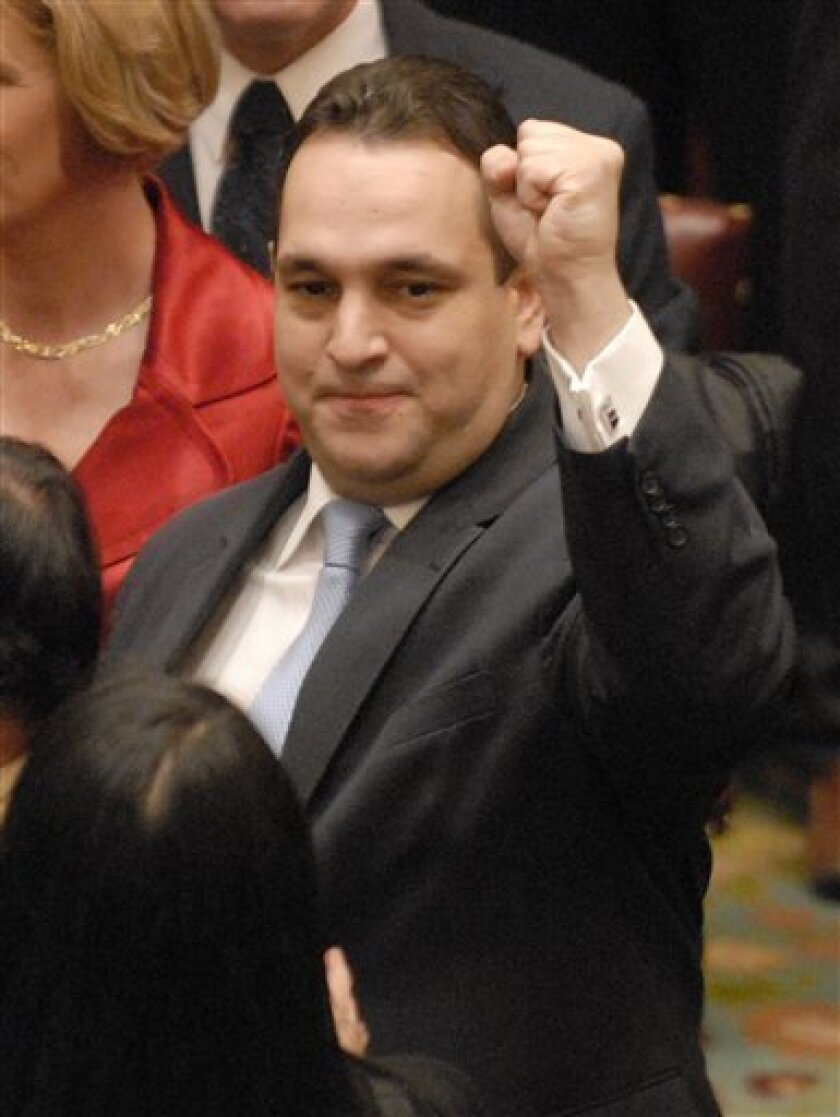 New York state Sen. Hiram Monserrate waves a fist to a supporter as he waits to be sworn into office at the Capitol in Albany, N.Y., Wednesday, Jan. 7, 2009.  (AP Photo/Tim Roske)