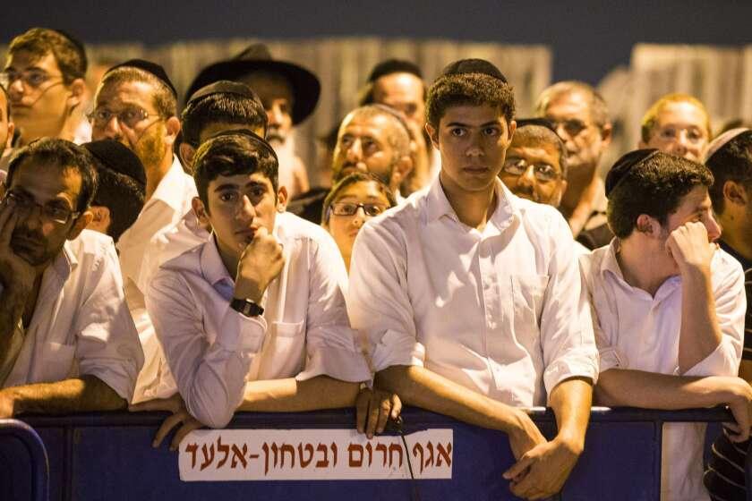 Israelis gather Monday outside the house of one of three Israeli teenagers.