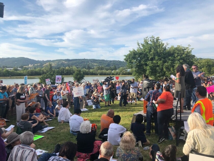 A vigil is held Monday outside Sheridan Federal Correctional Institutionin Sheridan, Ore., where migrants are allegedly being denied access to lawyers.