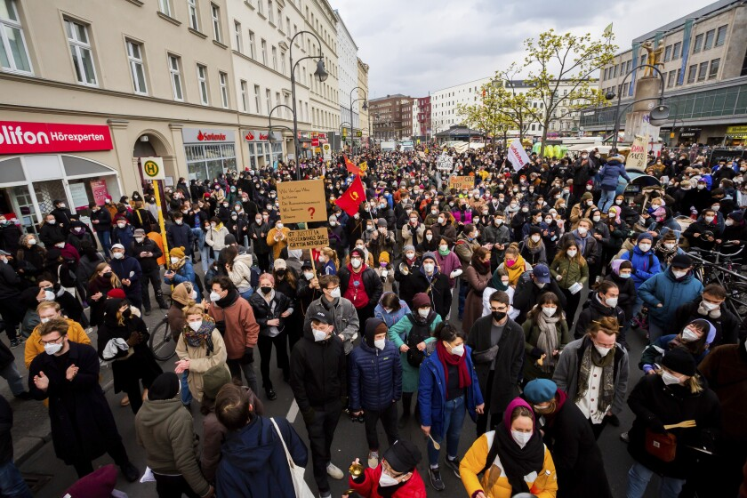 """Participants gather for a mass rally to protest against a court ruling removing a rent cap in Berlin, Germany Thursday April 15, 2021. The alliance """"Together against displacement and #Mietenwahnsinn"""" gathered Thursday to protest after the court overturned the rent cap. (Christoph Soeder/dpa via AP)"""