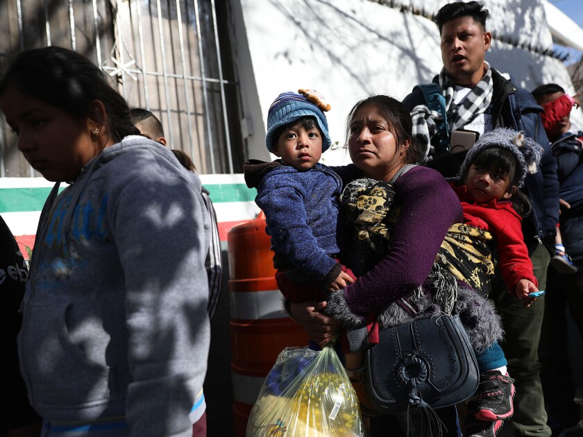 Migrants from Honduras, Mexico, Cuba and Guatemala wait to turn themselves in to U.S. Customs and Border Protection agents in Ciudad Juarez, Mexico. U.S. border officials finalized plans to require asylum seekers to remain in Mexico while their cases are considered in the United States.