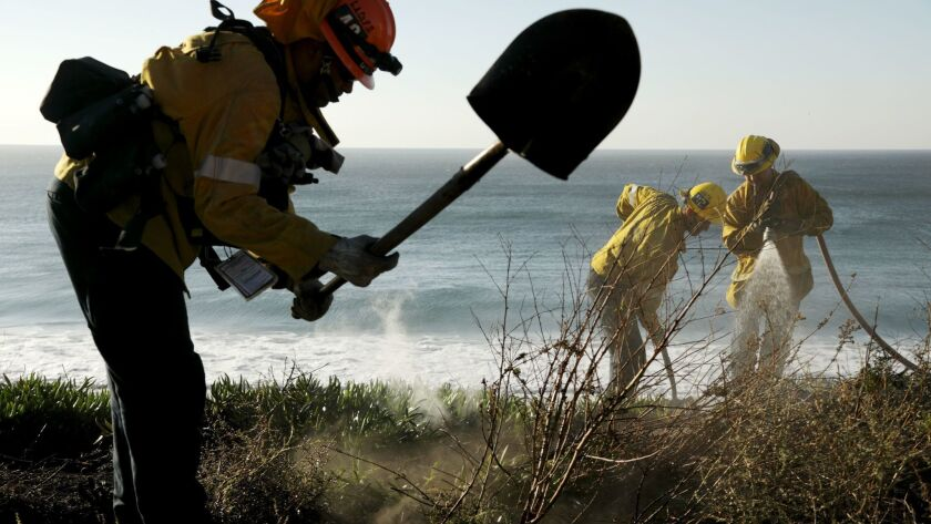 MALIBU, CA-NOVEMBER 12, 2018: Firefighters from the LA County Fire Department put out a flare up alo