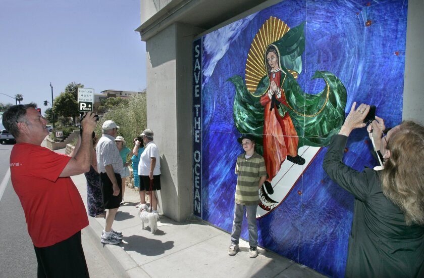 People gather to see the Madonna surfing mosaic on the railroad bridge support at Encinitas Boulevard. Local resident Brennan Savage photographs his son, Liam, 9.