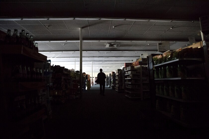 Shift supervisor James Quinn walks through a darkened CVS store during the power outage