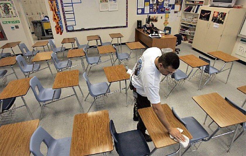Custodian Lou Rojas wiped desks at Chula Vista High School.