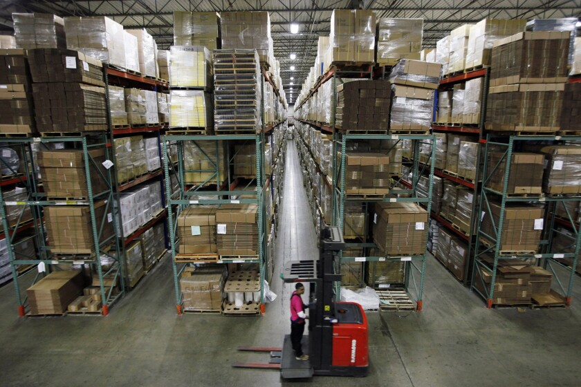 A warehouse employee drives a forklift used to move inventory inside the BSN Sports factory and warehouse in Dallas.