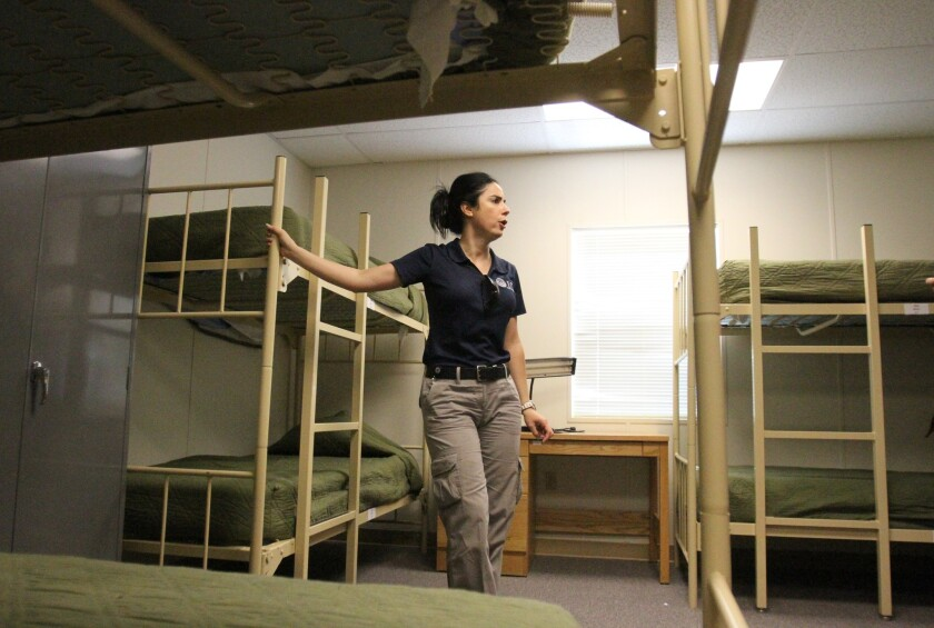 Barbara Gonzalez, public information officer for Immigration and Customs Enforcement, shows a dormitory where immigrant families are housed at the Artesia Residential Detention Facility in New Mexico.