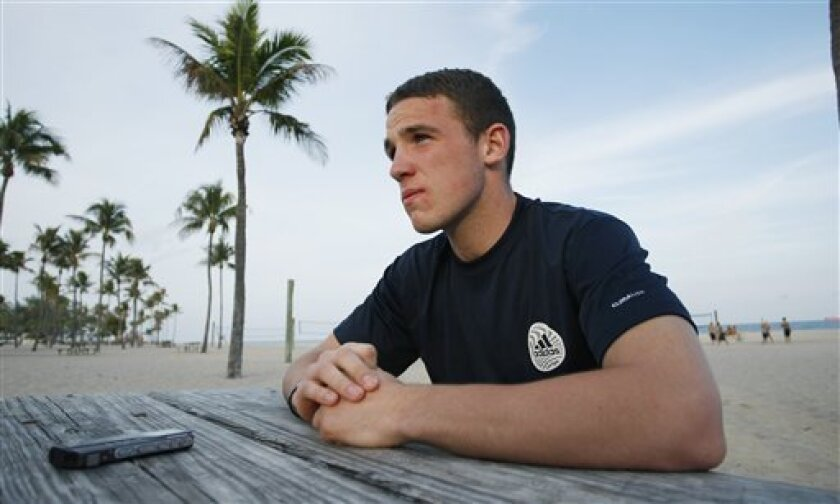 In this Monday, Jan. 10, 2011 photo, soccer player John Rooney sits on the beach in Fort Lauderdale, Fla. talking to the media. The back of Rooney's neck is beet red, which is what happens when an Englishman comes to Florida to escape the shadow of his famous brother, Wayne. A newcomer to the United States, John attended a Major League Soccer combine for the past five days and plans to play in the league this year. (AP Photo/J Pat Carter)