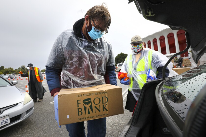 Union members Jacob De Wilde, left, and Lesli Lytle on Friday loaded a car with food for people struggling from the impact of coronavirus closings.