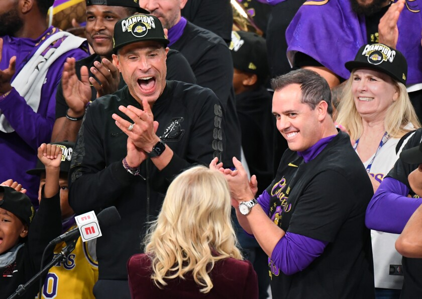 Rob Pelinka, left, and coach Frank Vogel, facing Jeanie Buss, clap in celebration of the Lakers win.