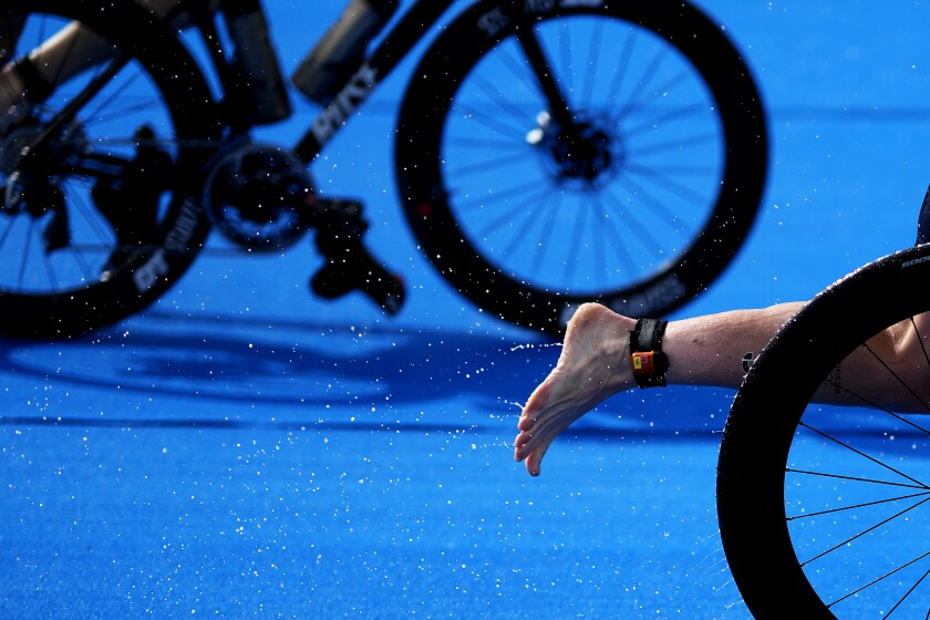 Water comes off the foot of Jessica Learmonth, of Britain, as she transitions in the rain from the bike to the running leg during the women's individual triathlon at the 2020 Summer Olympics, Tuesday, July 27, 2021, in Tokyo. (AP Photo/David Goldman)