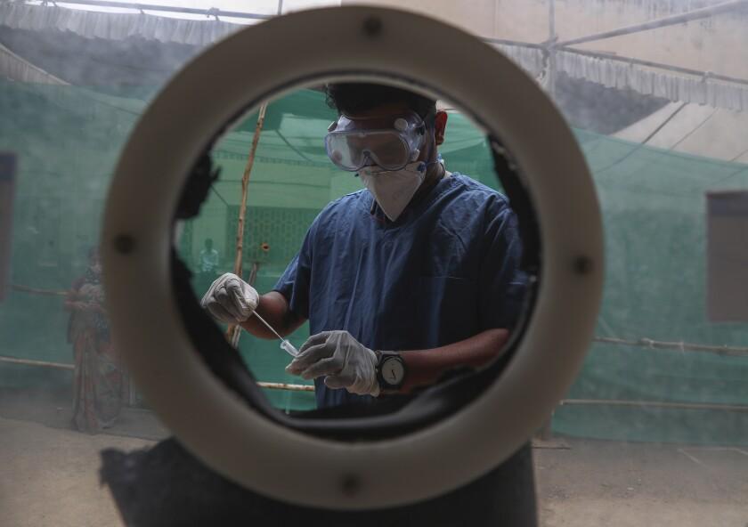 En esta imagen de archivo, tomada el 12 de abril de 2021, un sanitario toma una muestra nasal en un centro de pruebas de detección del COVID-19 en Hyderabad, India. (AP Foto/Mahesh Kumar A., archivo)