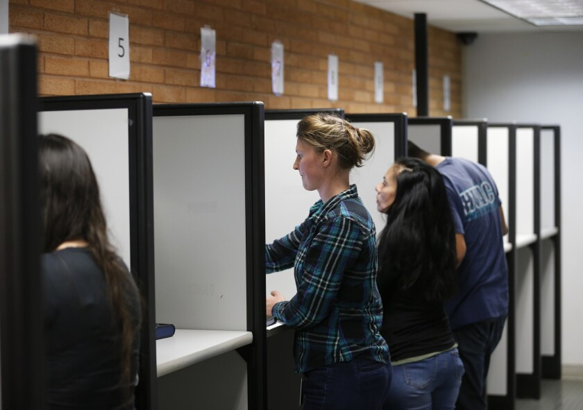 Glenn Woerndle, center, of Orange, registers to vote and takes her driver's test using a touch-screen machine in Santa Ana.