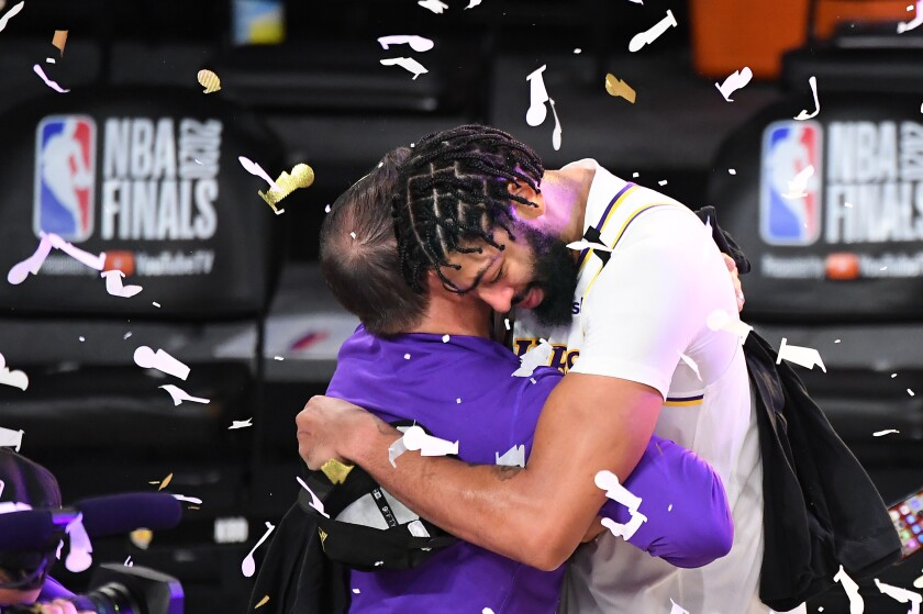 Lakers star Anthony Davis embraces coach Frank Vogel after winning the NBA title on Sunday.