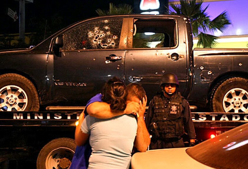 Family members of one of the slain state policemen console each other after seeing the pockmarked pickup the officers had been riding in when they were attacked in central Culiacan. The assailants, most likely cartel hitmen, escaped. At least 10 people died in 24 hours ending Wednesday night in Culiacan, in Sinaloa state, which has become a hub of violence since the federal government launched a crackdown against drug gangs.