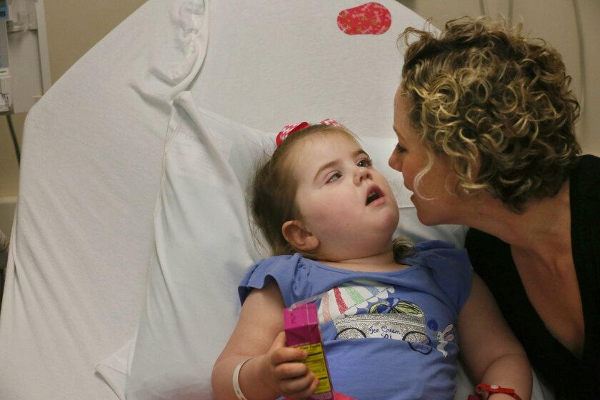San Diego, CA. March 24, 2016 | Teal Guion gives her daughter Gemma a kiss after she drank yet another box of juice during their regular visit to their doctor John Crawford at Rady Children's Hospital Thursday. Gemma's treatment has been personalized using genetic information from her tumor. Rady's