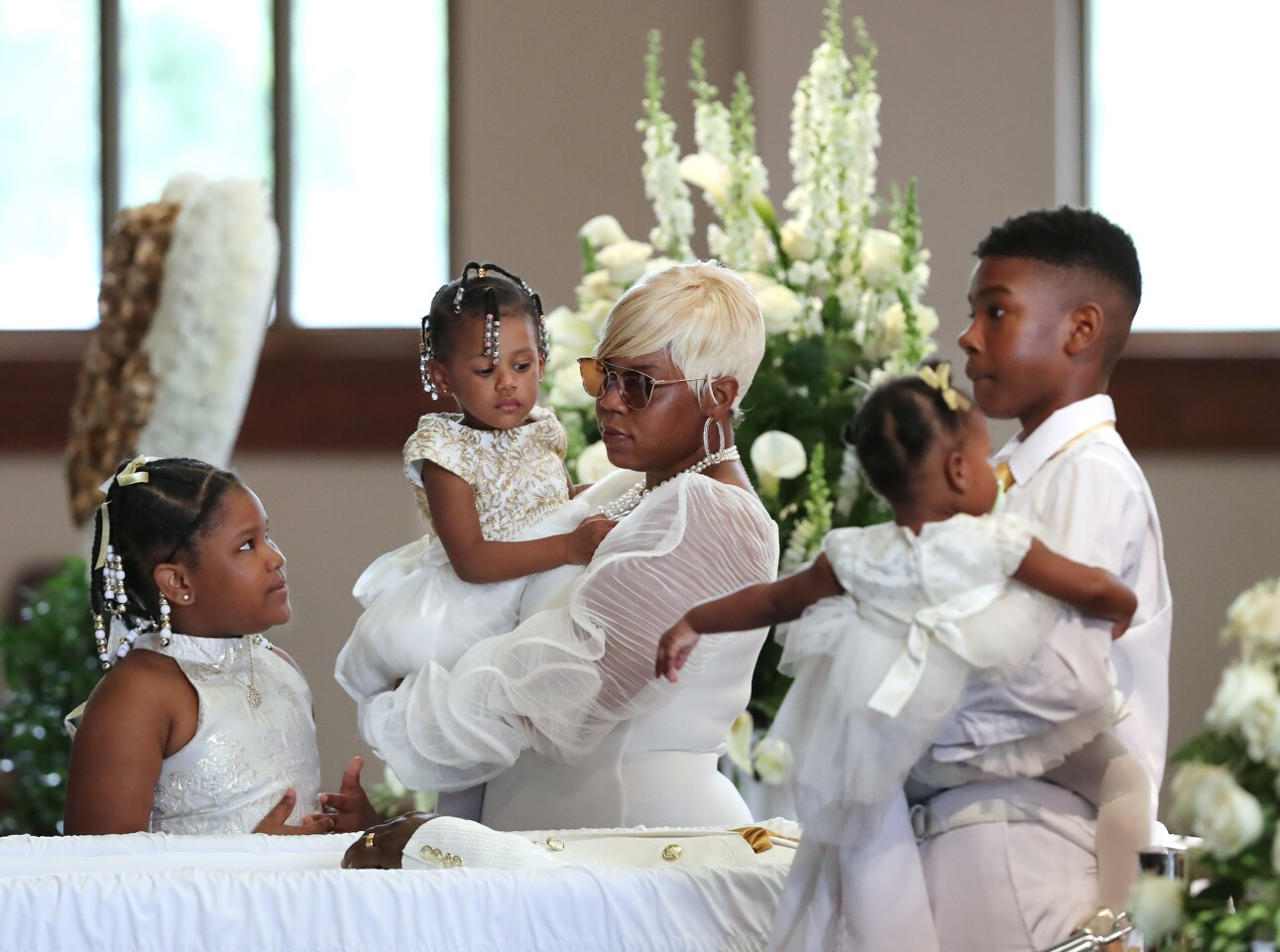 """ATLANTA, GEORGIA - JUNE 23: Tomika Miller, wife of Rayshard Brooks, holds their 2-year-old daughter Memory while pausing with her children during the family processional at his funeral in in Ebenezer Baptist Church on June 23, 2020 in Atlanta. Brooks, 27, died June 12 after being shot by an officer in a Wendy's parking lot, sparking protests in Atlanta and around the country. The Rev. Raphael G. Warnock, senior pastor of Ebenezer, said """"Rayshard Brooks wasn't just running from the police. He was running from a system that makes slaves out of people. A system that doesn't give ordinary people who've made mistakes a second chance, a real shot at redemption"""" (Photo by Curtis Compton-Pool/Getty Images)"""