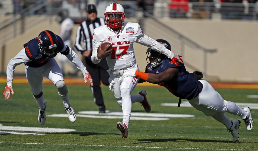 New Mexico quarterback Lamar Jordan, center, is sacked by UTSA safety Michael Egwuagu during the first half of the New Mexico Bowl on Saturday.