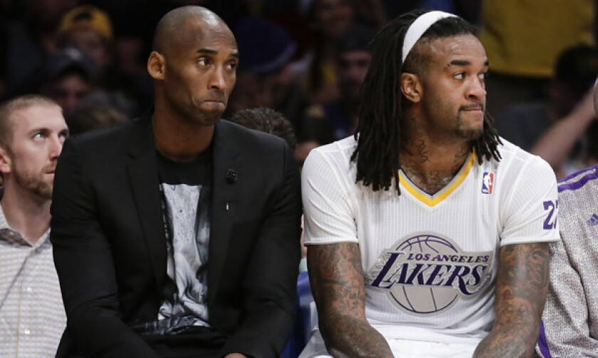 Injured Lakers star Kobe Bryant, left, and teammate Jordan Hill watch from the bench during the Lakers' Christmas Day loss to the Miami Heat at Staples Center. The Lakers' struggles have been reflected in television ratings for their games.