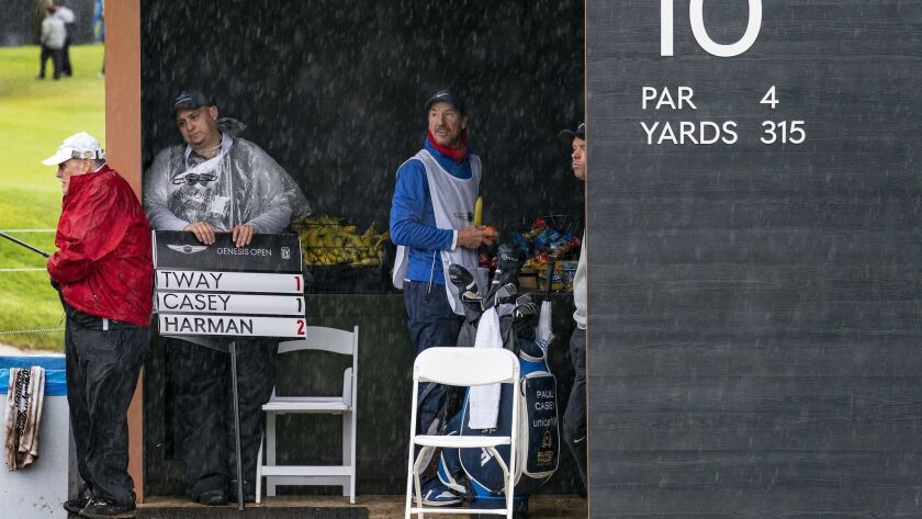 The sign guy takes refuge with the caddies in a snack hut at the 10th tee during a downpour in the first round of the Genesis Open at Riviera Country Club on Thursday in Pacific Palisades. Play was suspended for more than six hours due to rain.
