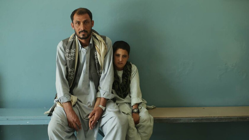 """A victim of a U.S. airstrike and his son in Kabul in 2015, seen in the documentary """"National Bird."""""""