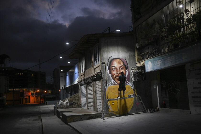 Street artist Wolfgang Salazar works on his mural featuring Venezuelan athlete Yulimar Rojas, in the Boleita neighborhood of Caracas, Venezuela, Saturday, Jan. 2, 2021. Salazar said he chose to paint Rojas because she embodies the potential of Venezuelan greatness. (AP Photo/Matias Delacroix)