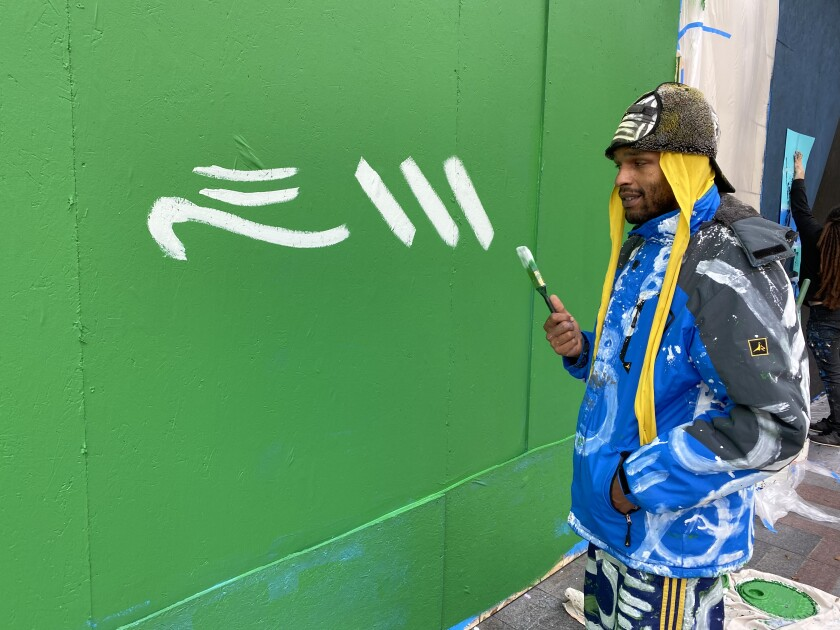 Malcolm Procter starts painting a mural on a boarded-up window covering a shattered Nordstrom window in downtown Seattle.