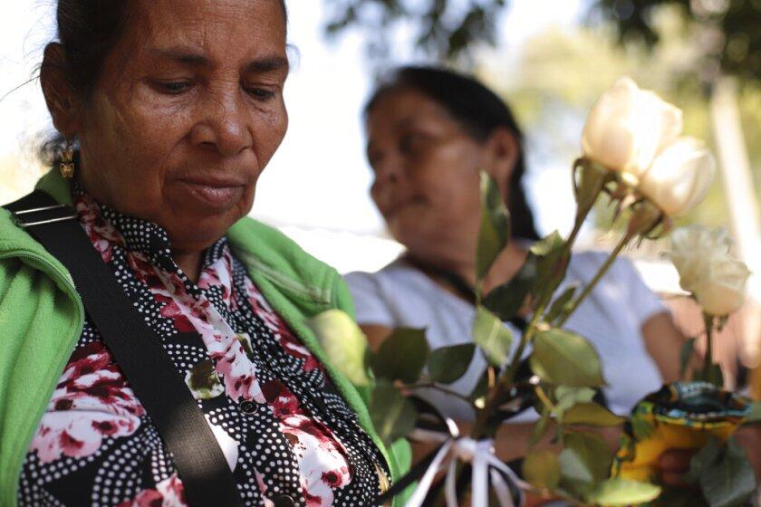 Juana de Jesús Regaleño Bonilla, de 66 años, sostiene rosas blancas mientras espera con sus familiares para recibir seis pequeños ataúdes que contienen restos de los familiares que perdió en una masacre de 1982, en San Salvador, El Salvador, el jueves 23 de enero de 2020. (AP Foto/Salvador Melendez)