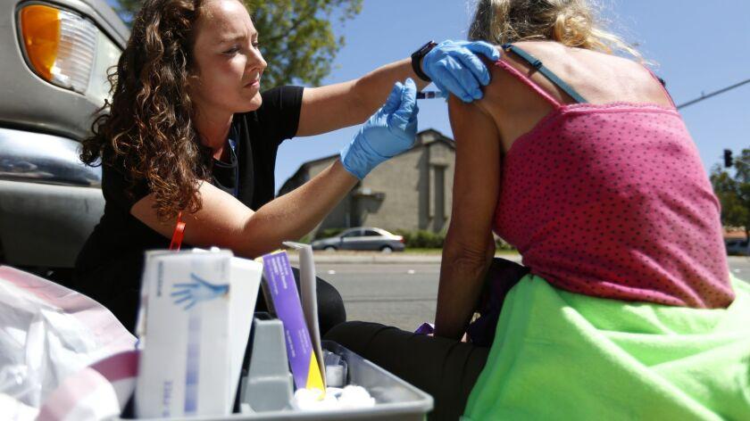 County of San Diego Public Health Nurse Tyler Eickholt gives a Hepatitis A shot to a homeless woman in El Cajon on Thursday.