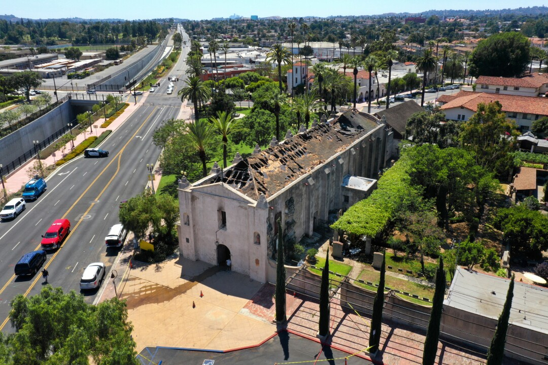 An aerial photograph shows the burned-out roof of the San Gabriel Mission