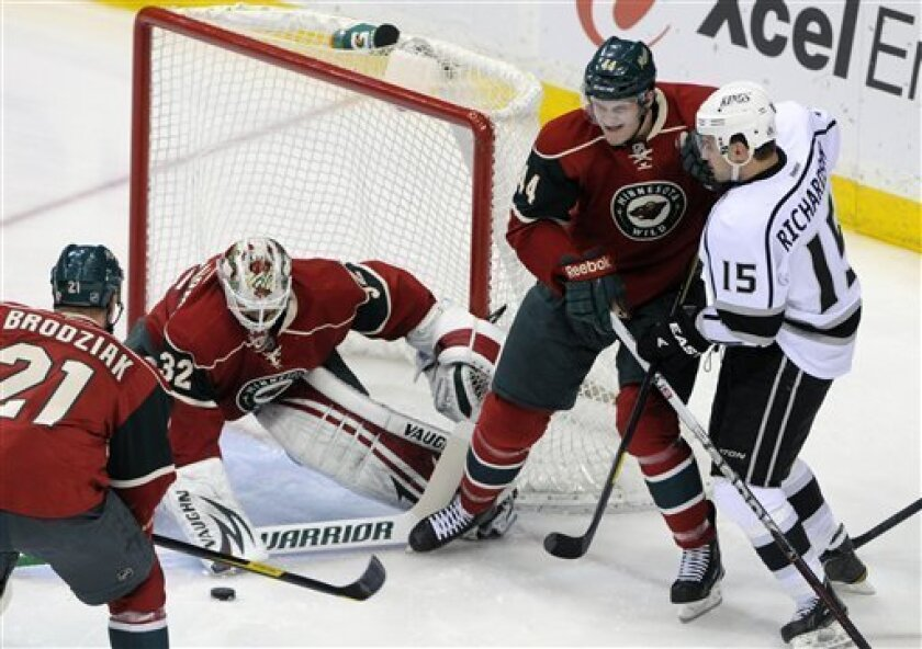 Minnesota Wild goalie Niklas Backstrom (32), of Finland, stops a shot as Wild's Justin Falk, second from right, keeps Los Angeles Kings' Brad Richardson, right, at bay in the first period of an NHL hockey game on Saturday, March 31, 2012, in St. Paul, Minn. (AP Photo/ Jim Mone)
