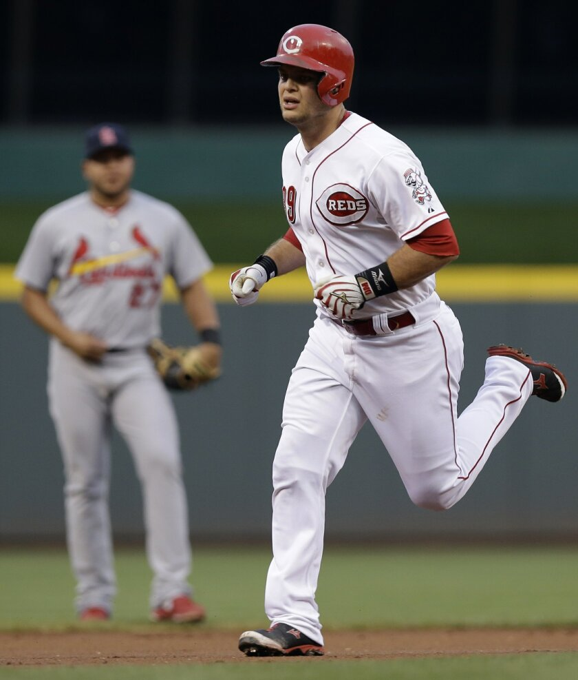 Cincinnati Reds' Devin Mesoraco rounds the bases past St. Louis Cardinals shortstop Jhonny Peralta, left, after hitting a solo home run in the first inning of a baseball game, Tuesday, Sept. 9, 2014, in Cincinnati. (AP Photo/Al Behrman)