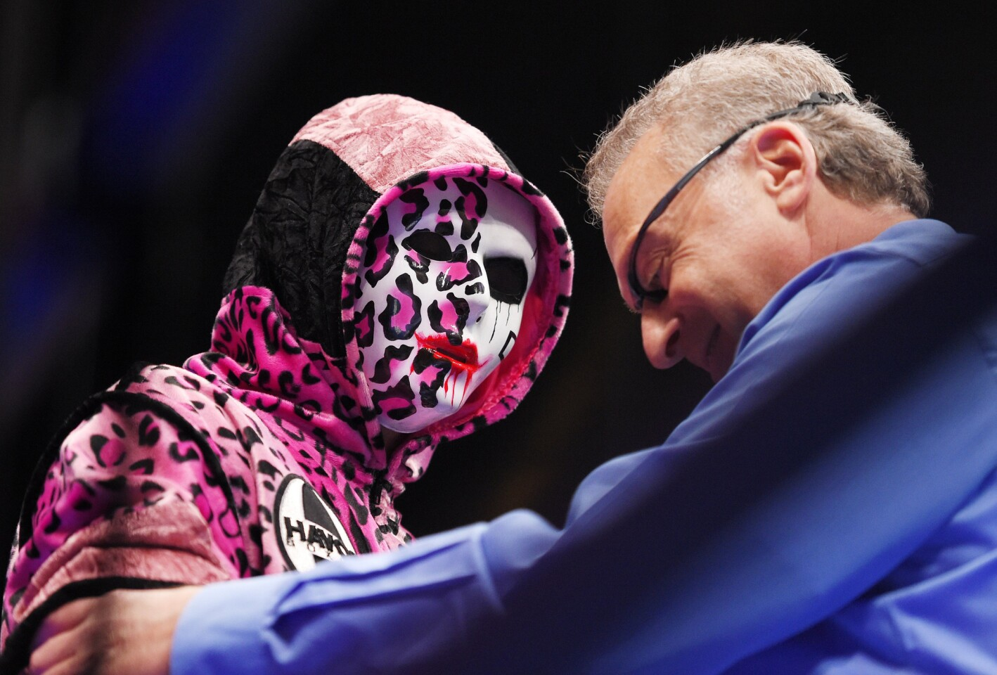 Referee Jack Reiss, right, talks with a mask-wearing Danny Garcia before his WBC welterweight title fight against Robert Guerrero.