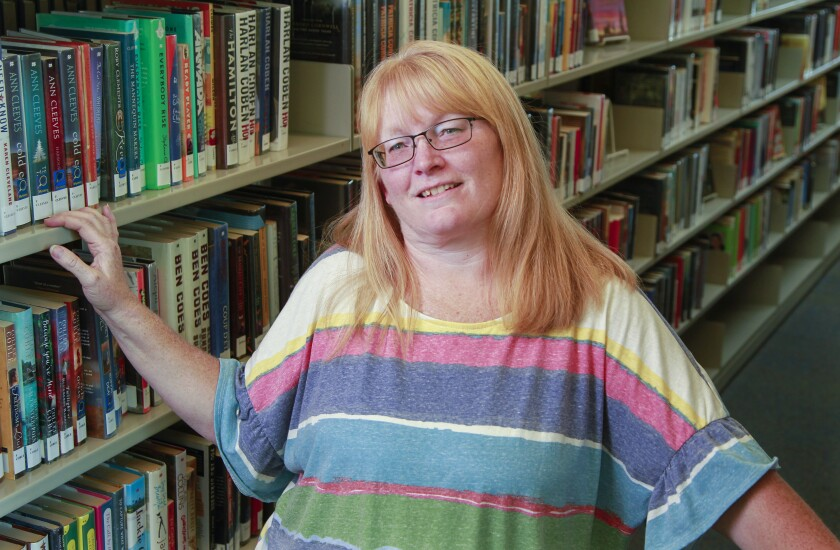 """Denise O'Neal, who is a board member for the San Diego Council on Literacy, which hosts its biggest fundraiser """"Eat. Drink. Read."""" on May 2, poses for a photo at the San Marcos Library."""