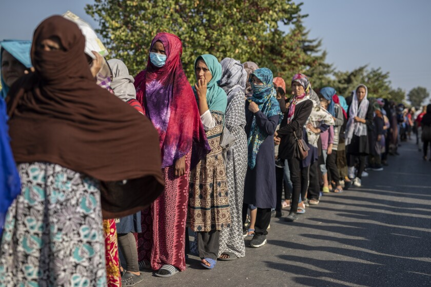 Migrants wait in a queue for food distribution near Mytilene town, on the northeastern island of Lesbos, Greece, Saturday, Sept. 12, 2020. Greek authorities have been scrambling to find a way to house more than 12,000 people left in need of emergency shelter on the island after the fires deliberately set on Tuesday and Wednesday night gutted the Moria refugee camp. (AP Photo/Petros Giannakouris)