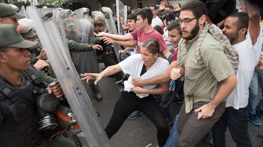 Venezuelan opposition activists scuffle with national guard personnel in riot gear during a protest in front of the Supreme Court in Caracas on Friday.