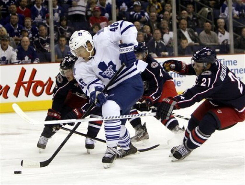 Toronto Maple Leafs' Joey Crabb (46) skates with the puck between Columbus Blue Jackets' Samuel Pahlsson (26) and James Wisniewski (21) during the first period of an NHL hockey game, Thursday, Nov 3, 2011, in Columbus, Ohio. (AP Photo/Terry Gilliam)