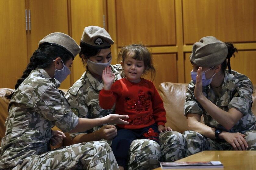 "Members of the Lebanese General Security forces play with an Albanian child during an operation to take them back home to Albania from al-Hol, northern Syria, at the Rafik Hariri International Airport in Beirut, Lebanon, Tuesday, Oct. 27, 2020. The repatriation of four children and a woman related to Albanian nationals who joined Islamic extremist groups in Syria ""is a great step"" to be followed by more repatriations, Albania's prime minister said Tuesday. (AP Photo/Bilal Hussein)"