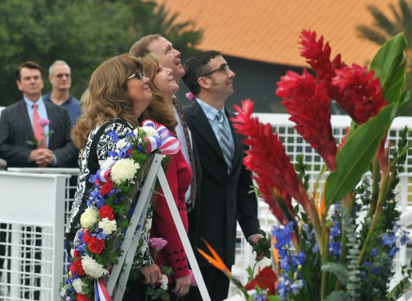 ADDS NAMES OF SUBJECTS - After placing a wreath, daughters and sons of astronauts who have died look up at the names of their loved ones on the Astronaut Memorial during a Day of Remembrance Ceremony on the 30th anniversary of the 1986 space shuttle Challenger tragedy, at the Kennedy Space Center Visitor Complex on Thursday, Jan. 28, 2016. From foreground are Sheryl Chaffee, daughter of Apollo 1 astronaut Roger Chaffee who died in the Apollo 1 fire on Jan. 27, 1967; Kathie Scobee Fulgham and Air Force Maj. Gen. Richard Scobee, children of Challenger commander Dick Scobee who died on Jan. 28, 1986; and Scott McAuliffe, son of Challenger schoolteacher Christa McAuliffe. (Tim Shortt/Florida Today via AP) NO SALES; MANDATORY CREDIT