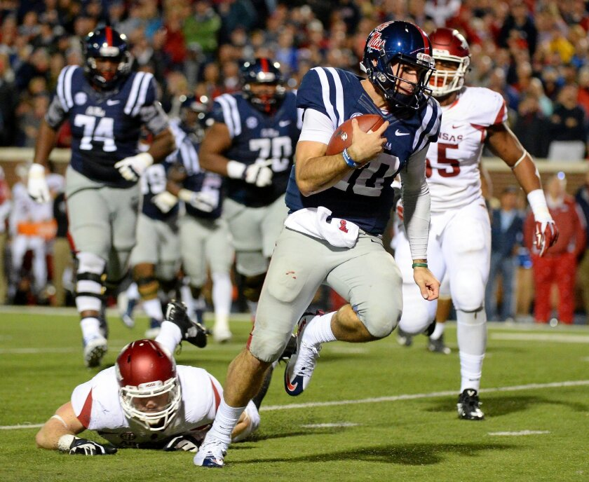Mississippi quarterback Chad Kelly (10) dodges Arkansas linebacker Brooks Ellis, bottom left, to run for an 8-yard touchdown during overtime of an NCAA college football game in Oxford, Miss., Saturday, Nov. 7, 2015. Arkansas won 53-52. (AP Photo/Thomas Graning)