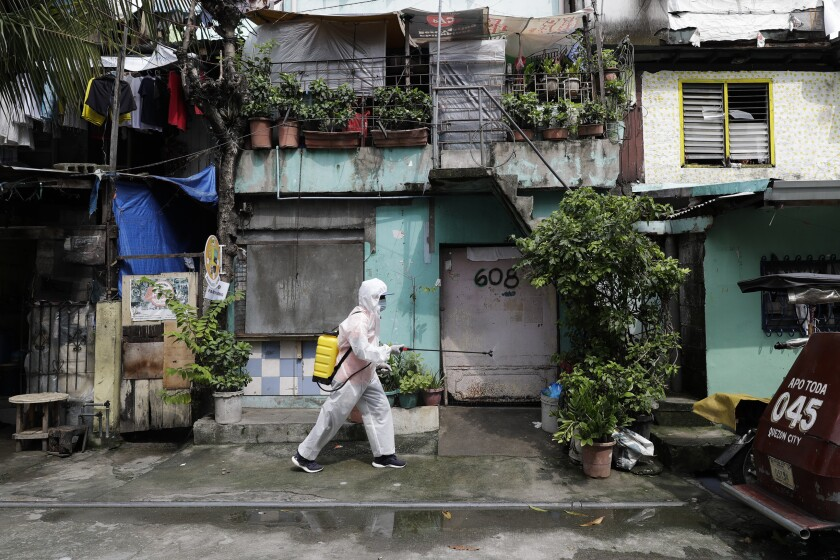 A man wearing a protective suit disinfects an area placed under stricter lockdown measures to curb the spread of COVID-19 in Caloocan city, Philippines on Friday, Aug. 14, 2020. The capital and outlying provinces is still under lockdown due to rising COVID-19 cases. (AP Photo/Aaron Favila)