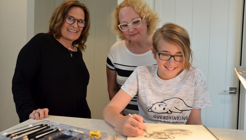 From left, teacher, Sonserae Leese and Jennifer Holm, look over Millie Hamel's shoulder during her