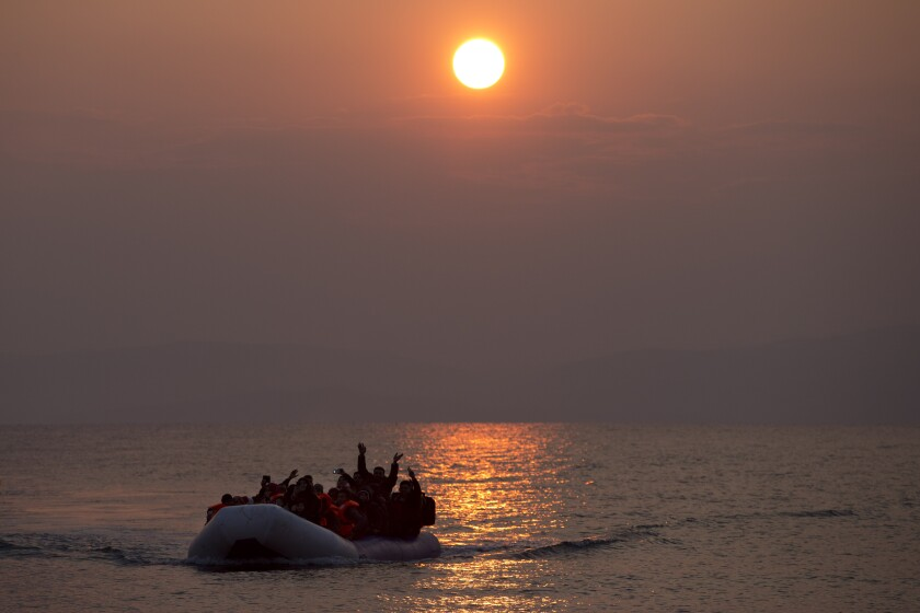File - In this Sunday, March 20, 2016, file photo, the sun rises as migrants and refugees on a dingy arrive at the shore of the northeastern Greek island of Lesbos, after crossing the Aegean sea from Turkey. The European Union's border and coast guard is under pressure following a series of allegations that it was involved in illegal pushbacks of migrants. Frontex is an increasingly powerful agency that monitors the 27-nation bloc's external borders. (AP Photo/Petros Giannakouris, File)