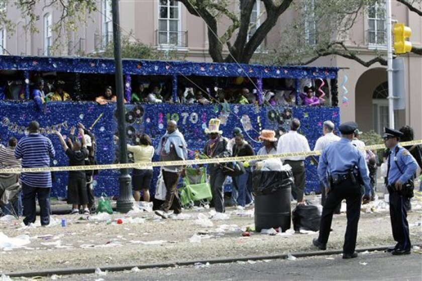 As a truck parade drives by and revelers walk past, New Orleans police officers stand guard at a crime scene where five people were shot and two suspects were taken into custody in a shooting incident that happened along the Mardi Gras parade route in New Orleans, Tuesday, Feb. 24, 2009. (AP Photo/