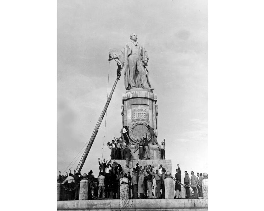 "FILE - In this Dec. 24, 1956 file photo, Egyptian civilians climb on the statue of Ferdinand de Lesseps, the French diplomat who was behind the construction of Egypt's Suez Canal, in Port Said, prior to blowing it up. A proposal to bring back the statue has stirred controversy in Egypt with many saying it would be a salute to colonial times and a ""humiliation"" to the memory of tens of thousands of Egyptian laborers who died while digging the waterway. The debate started when a newspaper reported in June 2020 that local authorities in the Mediterranean province of Port Said were thinking of returning the statue to where it once stood at the northern entrance of the canal. (AP Photo, File)"